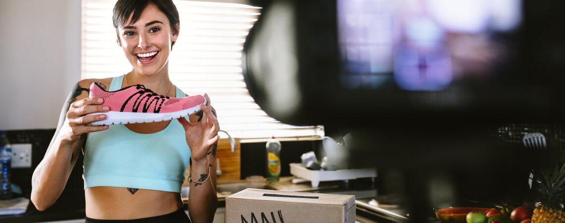 Frau hält Sneaker in die Kamera
