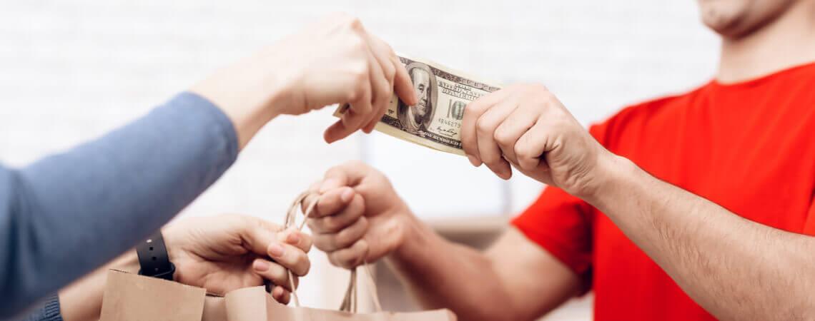 Frau nimmt Lieferung in Empfang und bezahlt per Nachnahme.