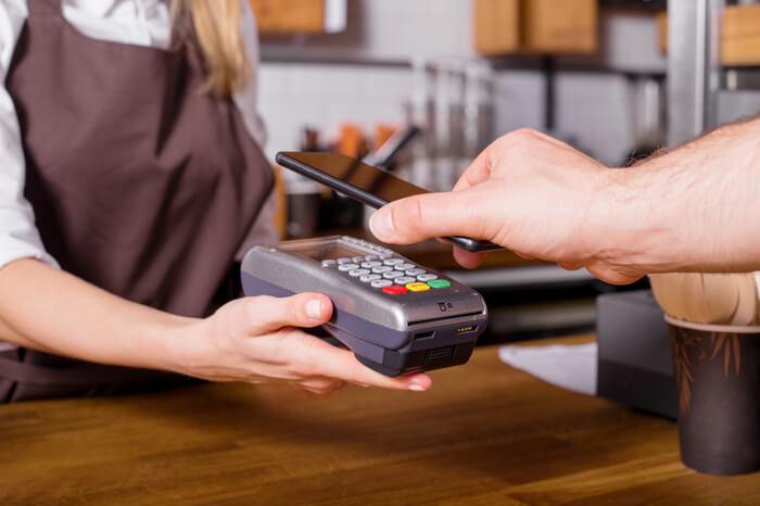 Smartphone bei mobilem Bezahlen über NFC-Gerät