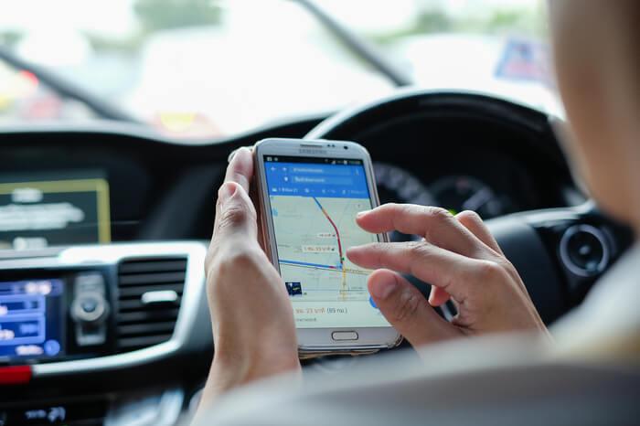 Frau nutzt Google Maps auf Smartphone im Auto