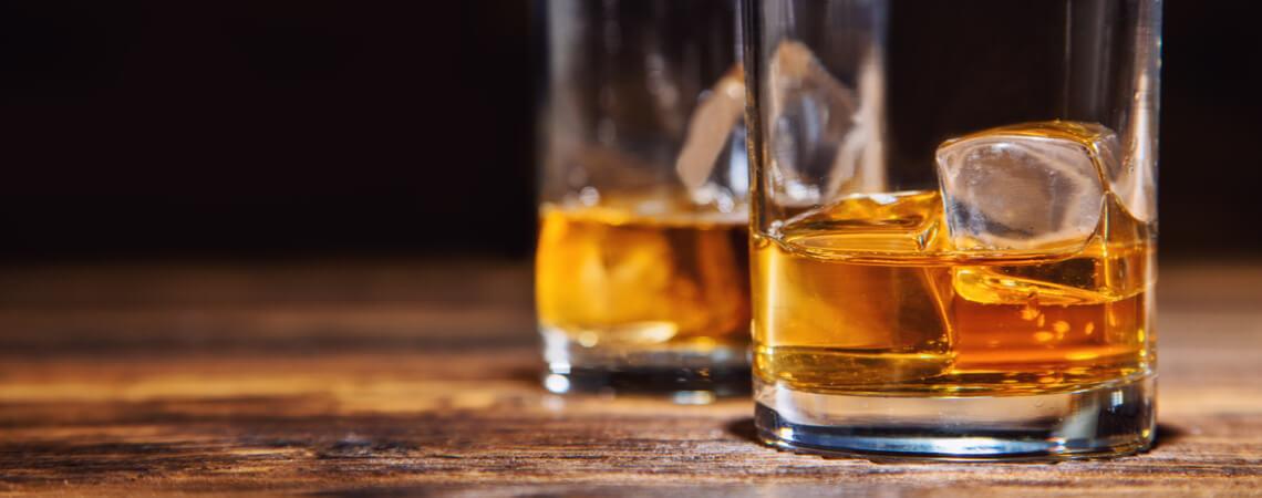 Zwei Gläser Whiskey mit Eiswürfeln.