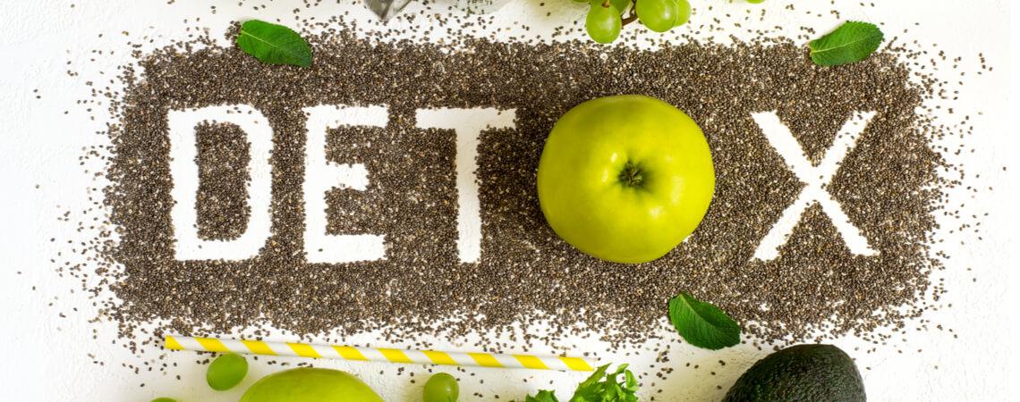 Das Wort Detox mit Chiasamen und grünem Obst ringsrum.