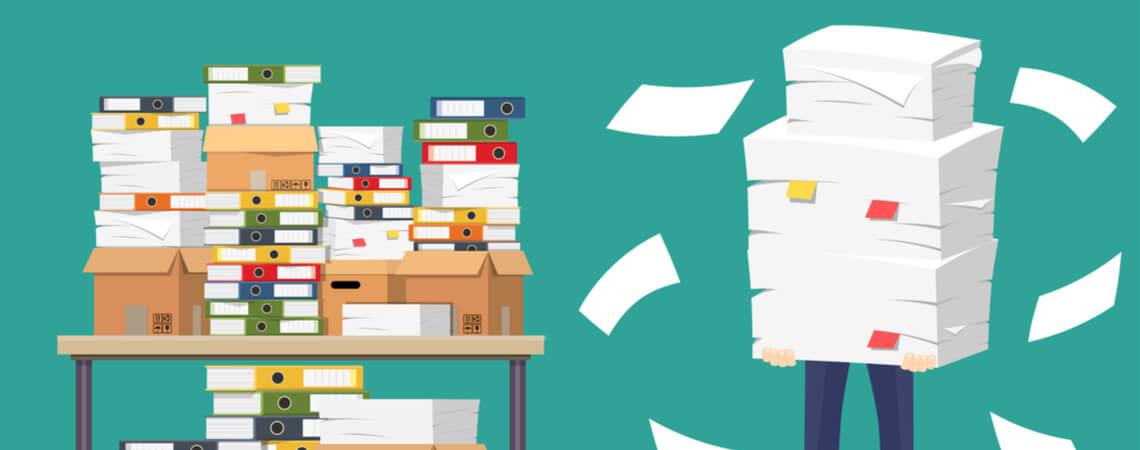 Person hält einen großen Stabel Papier, während sie neben einem mit Akten vollgepackten Schreibtisch steht.