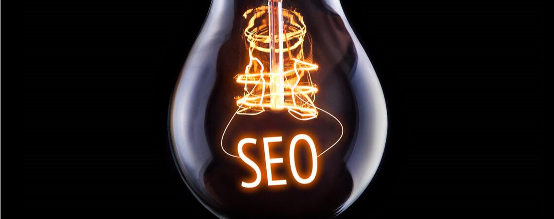 Das Wort SEO leuchtet in einer Glühbirne