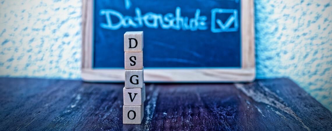 Tafel mit der Schrift Impressum und Datenschutz und im Vordergrund Würfel mit der Aufschrift DSGVO.