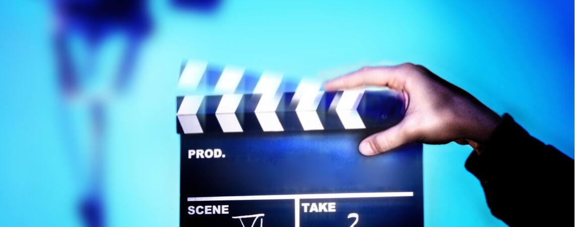 Hände halten Filmklappe an Filmset