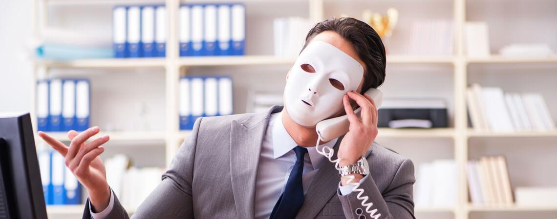 Person mit Maske vor Computer