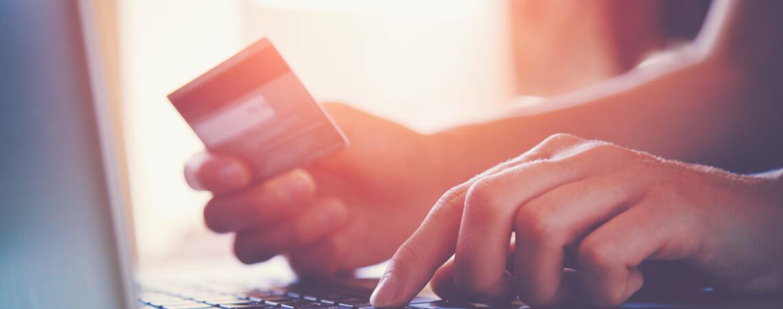 Frau mit Kreditkarte am Laptop