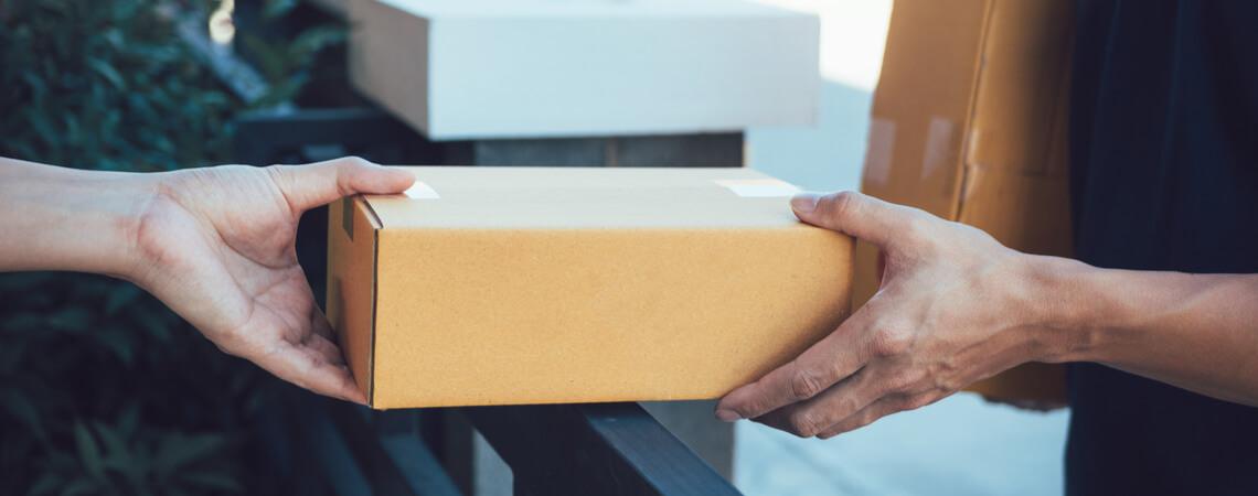 EIn Paket wird vom Zusteller an den Empfänger überreicht