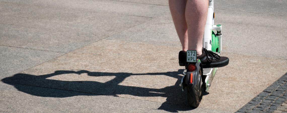 Mann fährt auf einem E-Scooter