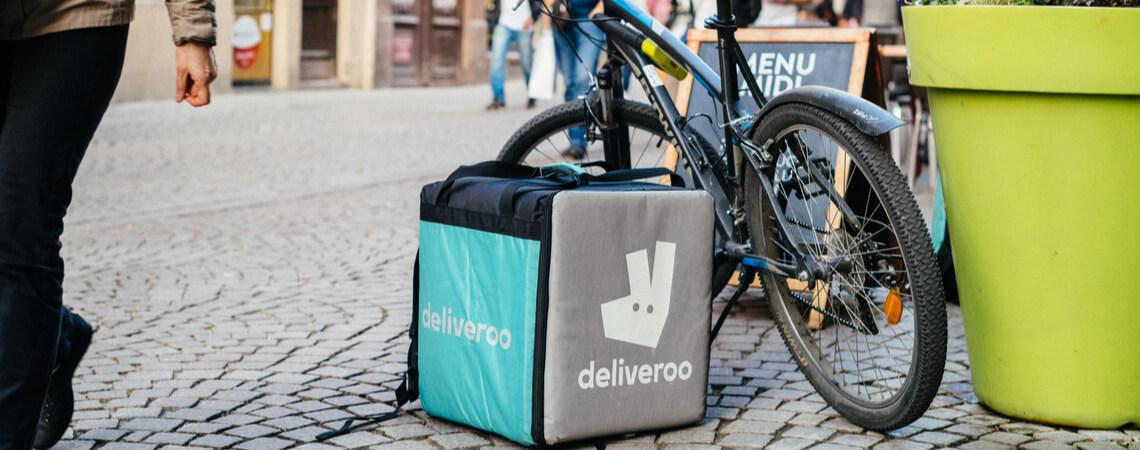 Abgelegter Deliveroo-Rucksack neben einem Fahrrad