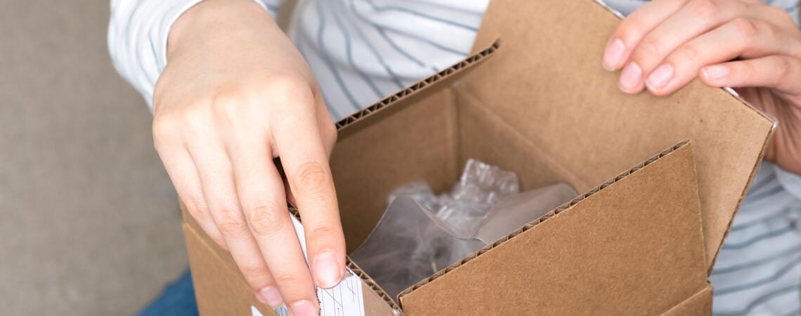 Frau packt ein Paket aus
