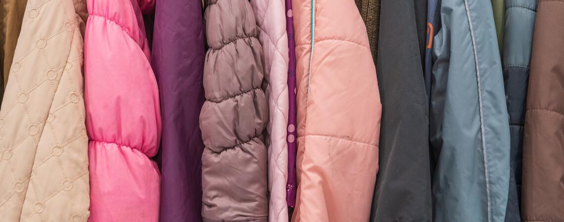 Verschiedene Jacken hängen auf einer Kleiderstange.