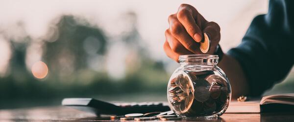 Hand füllt Münze in ein Glas. Daneben steht ein Taschenrechner.