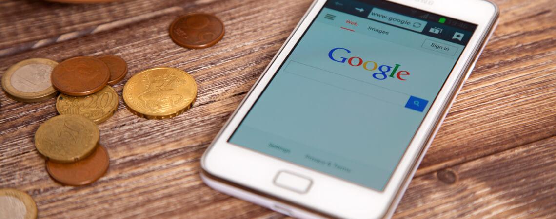 Google auf Smartphone mit Kleingeld