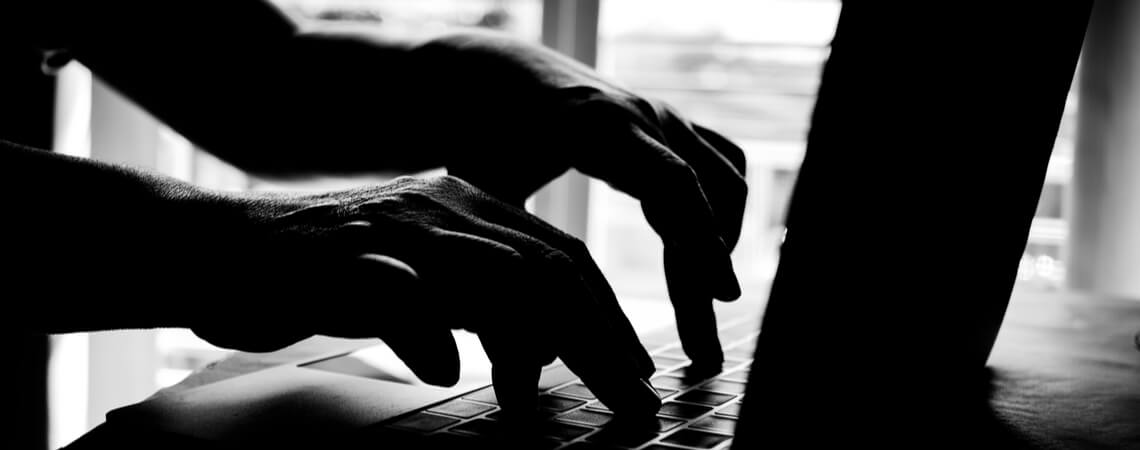 Licht und Schatten: Hände an einer Tastatur
