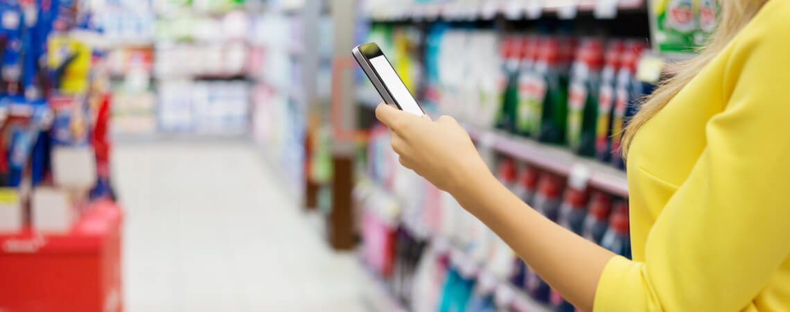 Kundin mit Smartphone im Geschäft