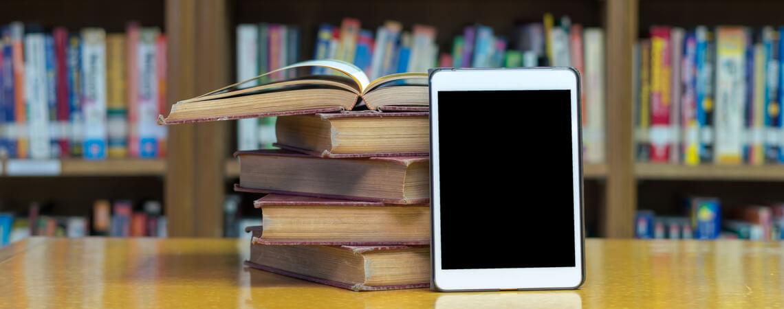 E-Book-Reader neben Bücherstabel