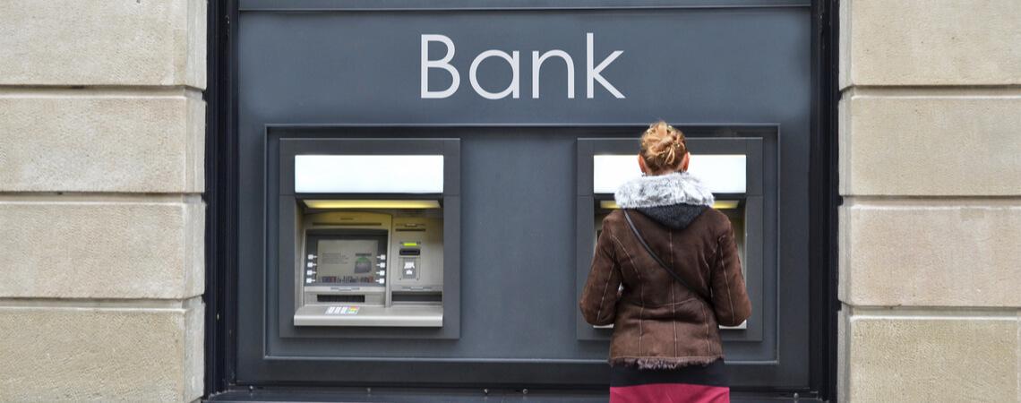 Frau steht vor Geldautomaten