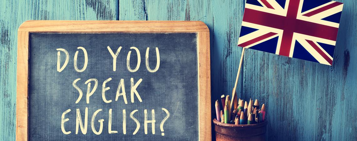 """Eine Tafel mit dem Text """"Sprichst du Englisch?"""". Daneben ein Topf mit Bleistiften und die Flagge des Vereinigten Königreichs auf einem Holzschreibtisch"""