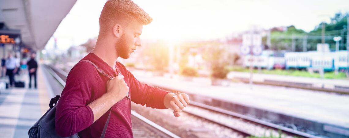 Mann schaut auf Uhr am Gleis