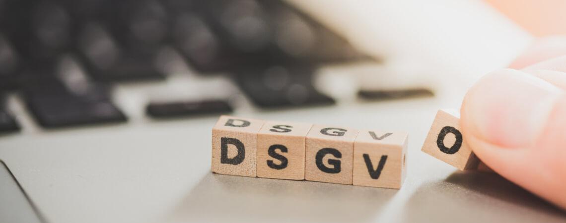 Holzwürfel mit DSGVO-Aufdruck auf Laptop