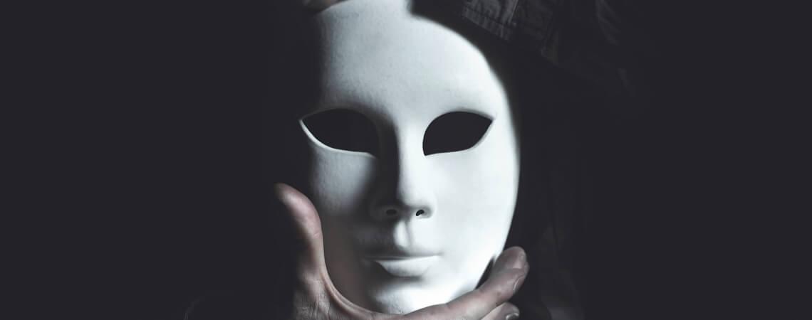 Fake: Mensch mit einer weißen Maske in den Händen