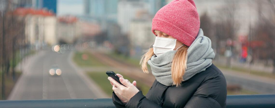 Frau mit Smartphone und Gesichtsmaske