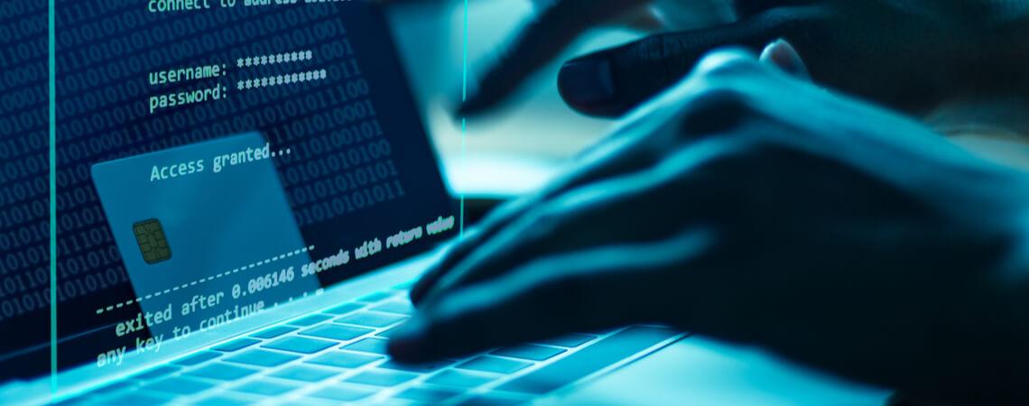 Online-Betrug: Hände an Tastatur im Dunkeln