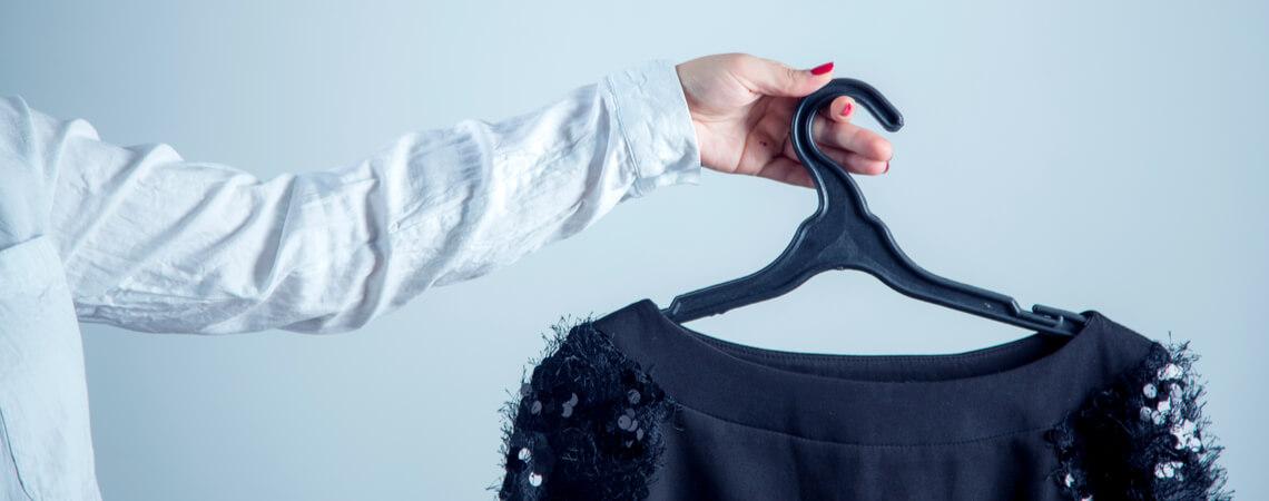 Hand hält Kleidung auf Kleiderbügel