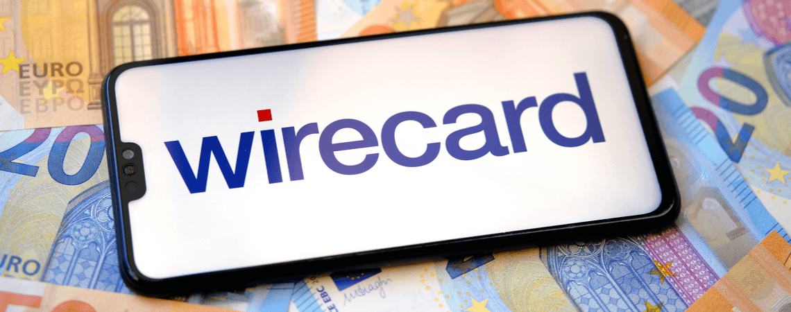 Wirecard-Logo auf einemSmartphone auf Geldscheinen