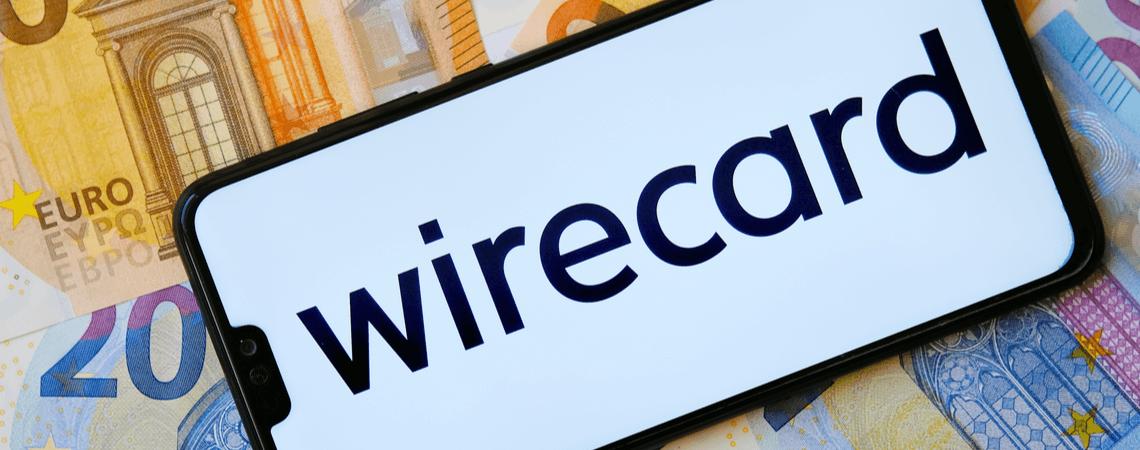 Wirecard-Logo auf einem Smartphone auf Geldscheinen