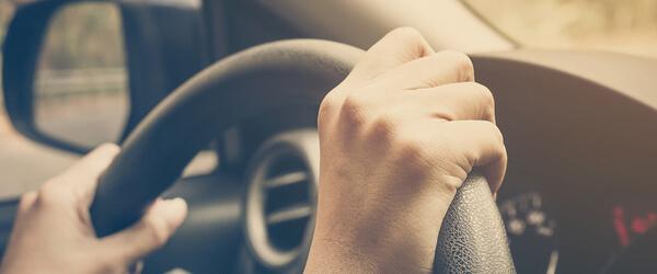 Im Auto: Hände an einem Lenkrad