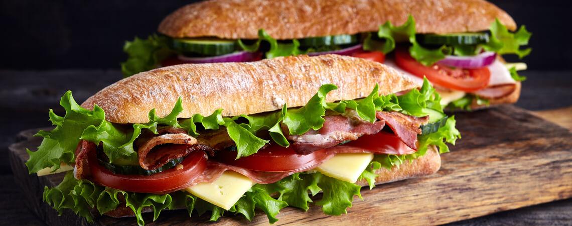 Zwei frische U-Boot-Sandwiches mit Schinken, Käse, Speck, Tomaten, Salat, Gurken und Zwiebeln auf Holzbrett