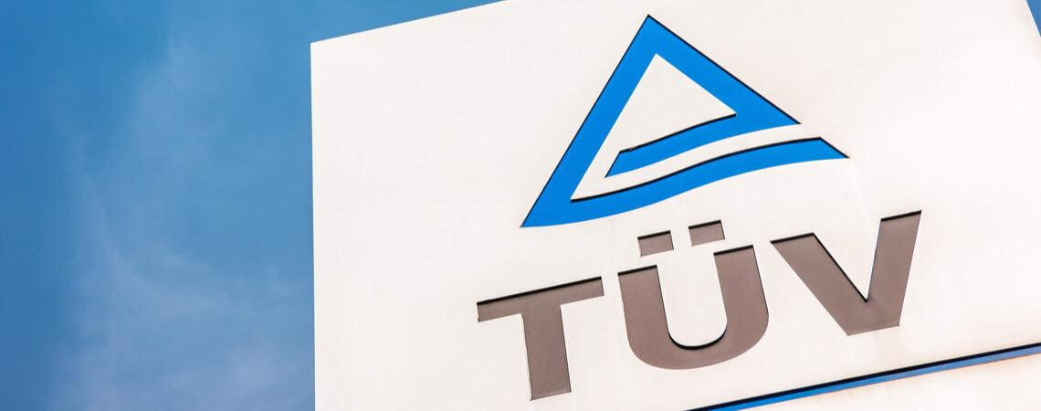 TÜV Logo vor Himmel