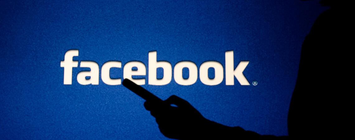 Mensch vor einem riesigen Facebook-Logo