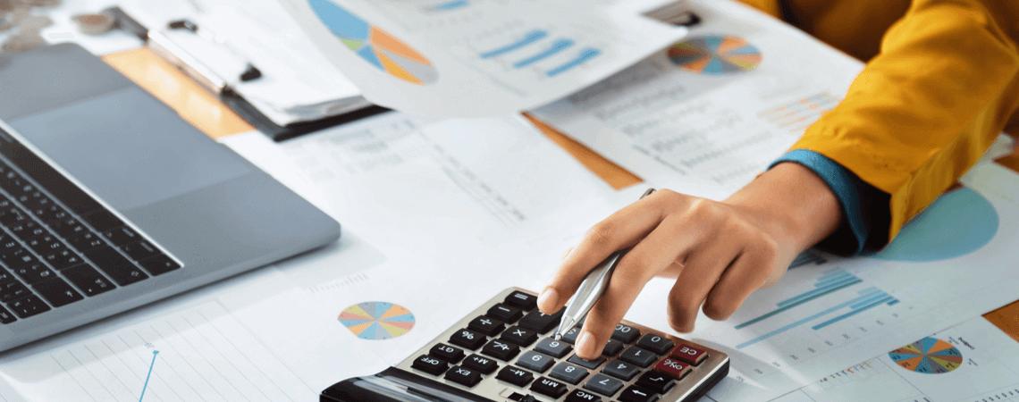 Frau mit Laptop, Taschenrechner, Finanzdiagramm
