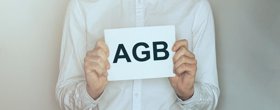Mann hält AGB-Schild
