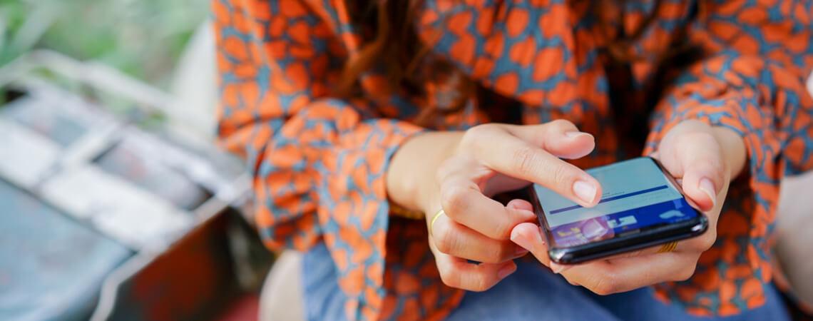 Frau surft aus Smartphone zu Facebook