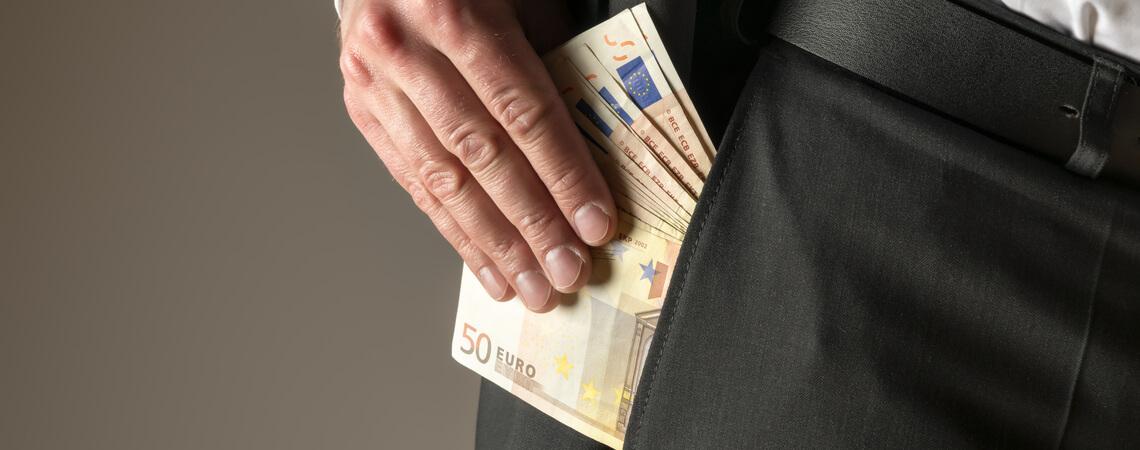 Mann steckt Geld in die Hosentasche