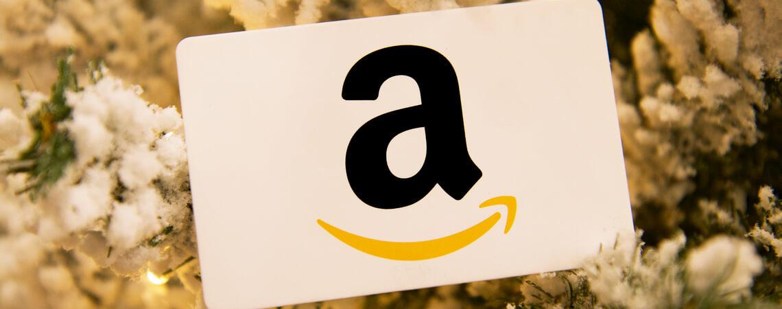 Amazon-Logo mit Weihnachtsbaum im Hintergrund