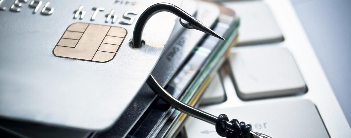Phishing mit Kreditkarte - Stapel von Kreditkarten mit Fisch-Haken auf der Computertastatur