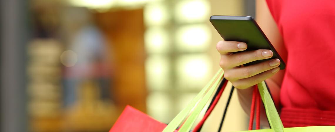 Frau mit Smartphone und Einkaufstaschen