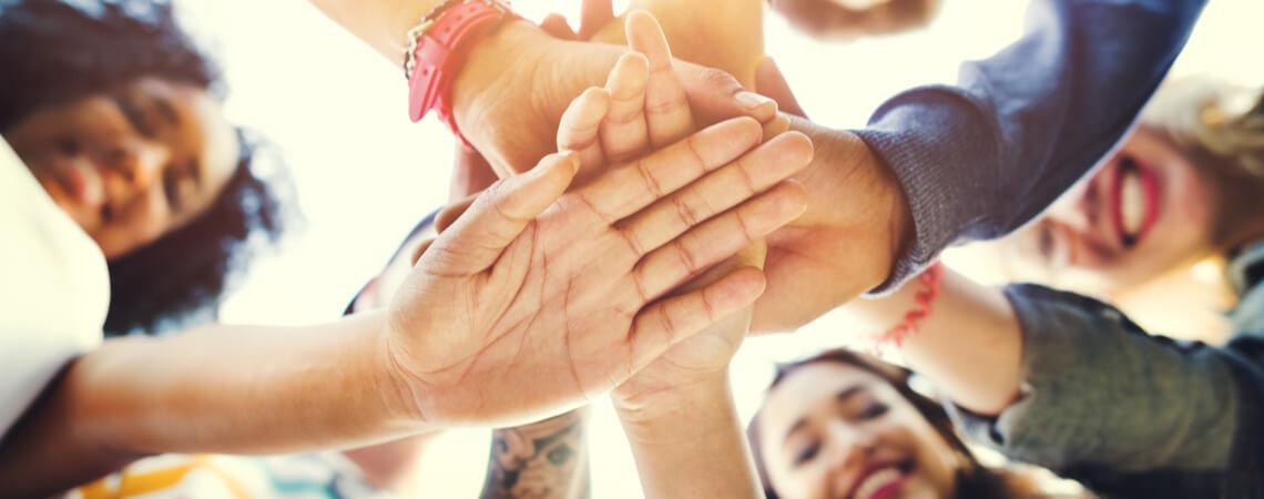 Gruppe von Leuten stapelt Hände übereinander