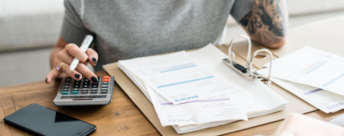 Frau macht an Couchtisch Steuererklärung