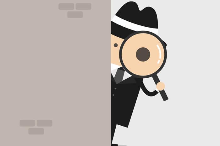 Detektiv, der eine Lupe hinter der Wand hält.