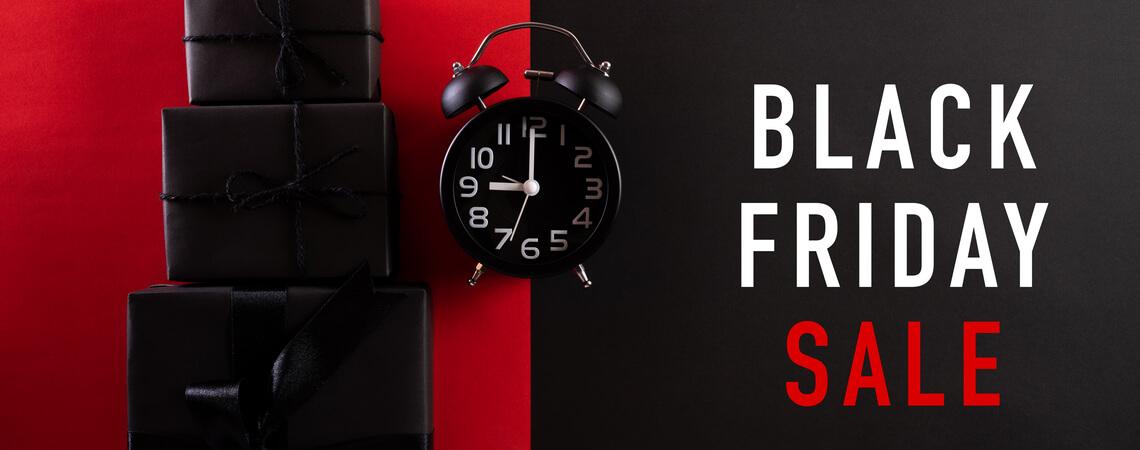 """Schwarze Geschenke, Schriftzug """"Black Friday Sale"""" und schwarzer Wecker"""