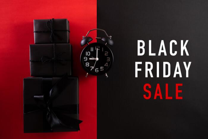 Schwarze Geschenke, Schriftzug Black Friday Sale und schwarzer Wecker