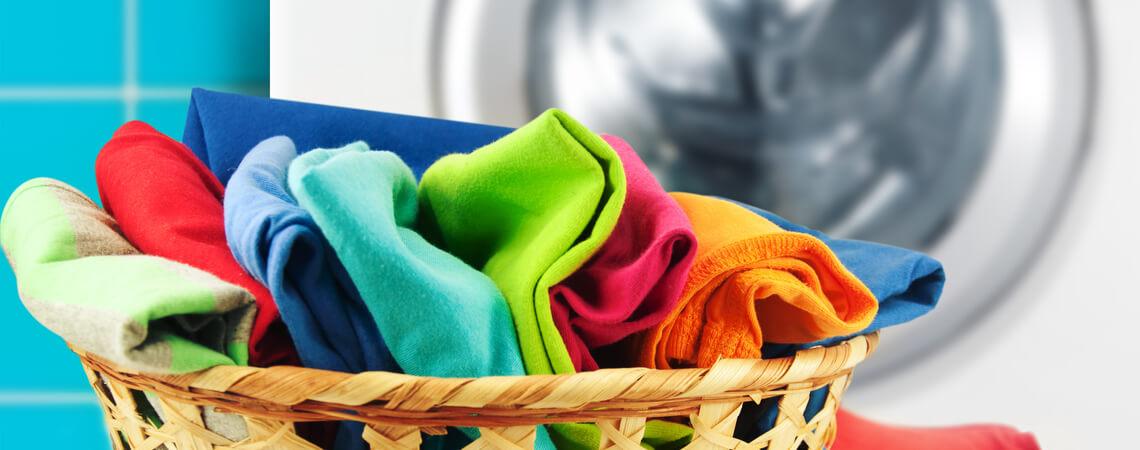 Stoffe in einem Korb, der vor einer Waschmaschine steht.