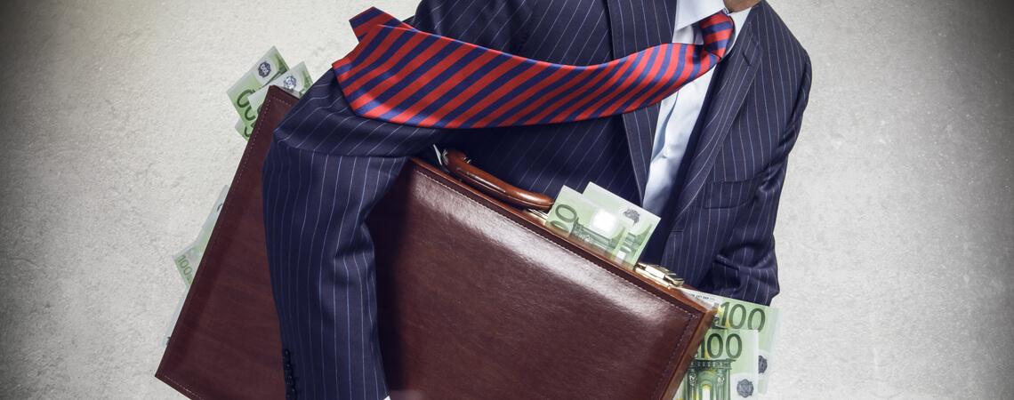 Mann in Anzug trägt Geldkoffer